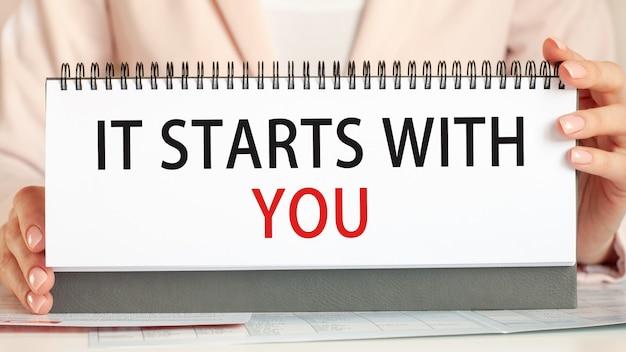 A mulher segura um papelão com as mãos com o texto começa com você