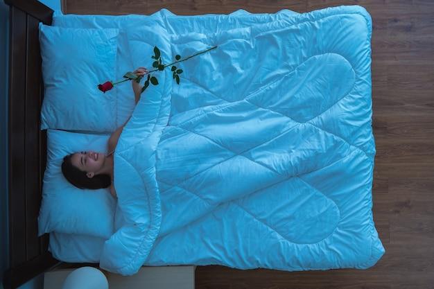 A mulher segurando uma rosa na cama. noite, noite, vista de cima