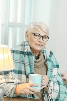 A mulher sênior envolvida em uma manta quadriculada está bebendo o chá em casa