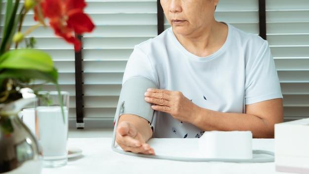 A mulher sênior está detectando a pressão sanguínea em casa