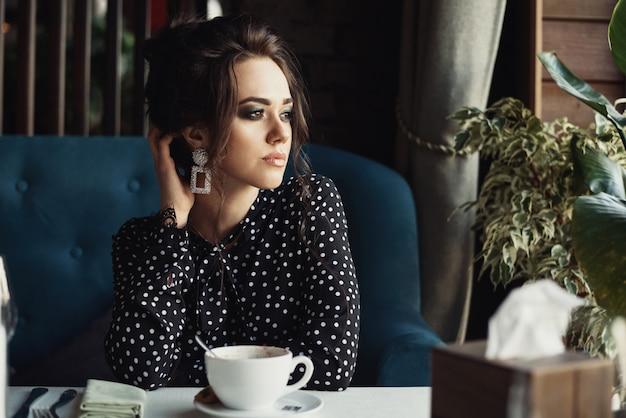 A mulher senta à mesa no café ou restaurante olha para a janela e bebe café
