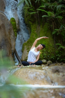 A mulher senta-se em zen da posição de lótus que gesticula. conceito de estilo de vida saudável e relaxamento.
