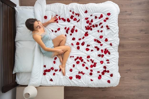 A mulher sentada na cama com pétalas de rosa. vista de cima