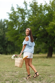 A mulher smilling nova bonita dentro com as flores na cesta de vime anda no parque verde do verão.