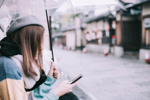 A mulher só com guarda-chuva está esperando a chuva na rua em japão.