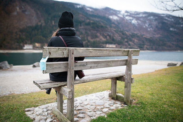 A mulher solitária sentada em um banco sozinha no parque olhando ao longe vista de trás