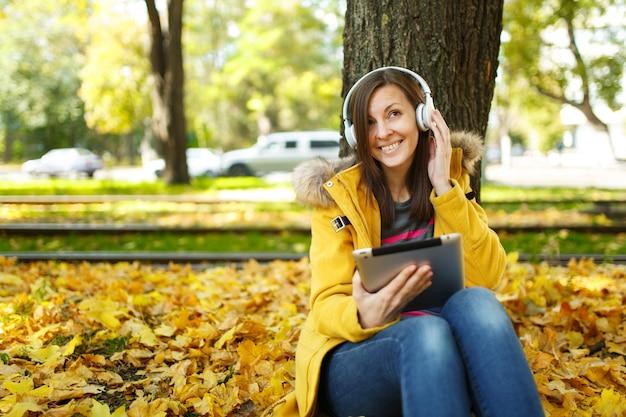 A mulher sorridente de cabelos castanhos com casaco amarelo e calça jeans sentada e ouvindo música debaixo de uma árvore com um tablet nas mãos e fones de ouvido no outono parque da cidade em um dia quente. folhas de outono dourado.