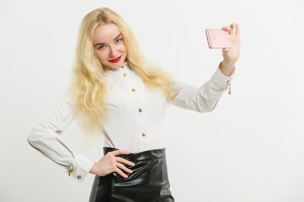 A mulher sorridente está apontando no smartphone em pé no fundo branco
