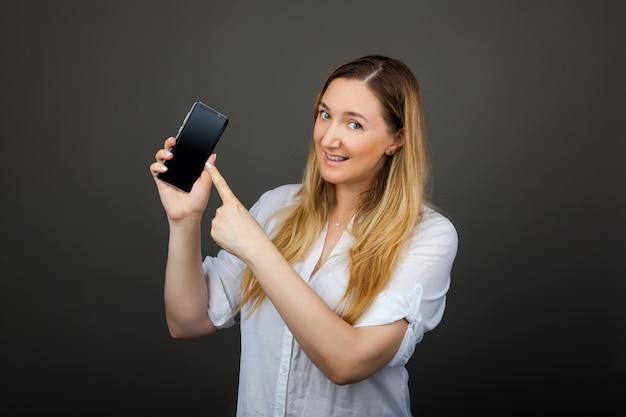 A mulher sorridente está apontando no smartphone em pé no fundo cinza.
