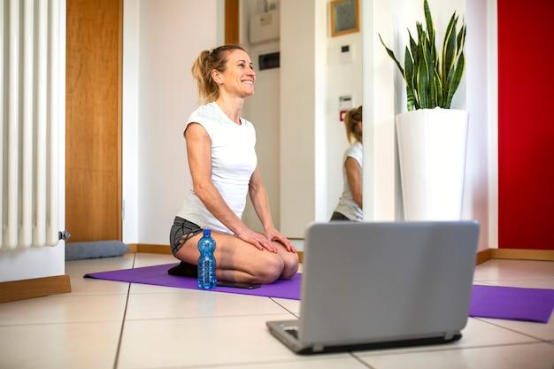A mulher sorridente na moderna sala de estar assiste a tutoriais de fitness na internet via laptop.