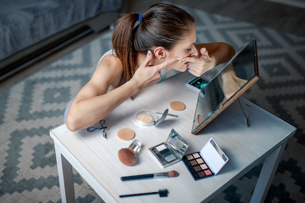 A mulher squashes pimples na face. mulher senta-se antes de espelho. mulher fazendo maquiagem.