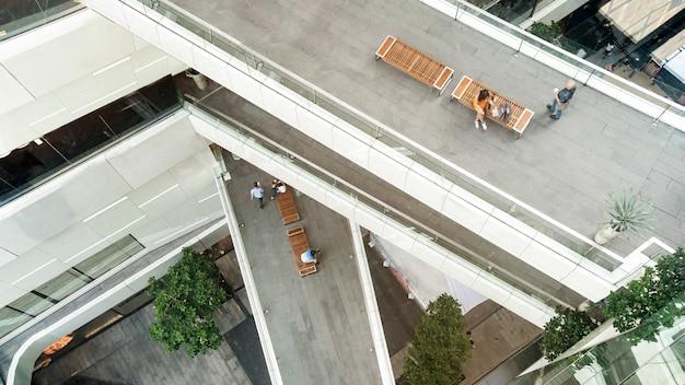 A mulher superior da forma da vista aérea com o saco de compras usa o smartphone senta-se no banco de madeira no pedestre da passagem.