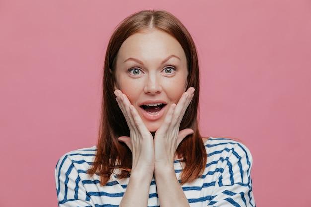 A mulher surpreendida feliz positiva vê algo inacreditável, mantém as mãos nas bochechas