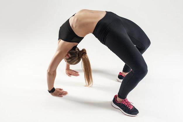 A mulher tem coluna elástica. pose da ponte. mulher atlética fazendo ioga. foto de estúdio, fundo cinza