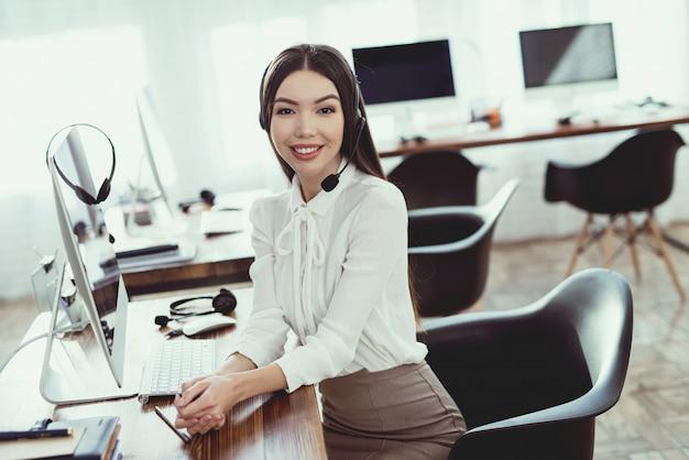 A mulher tem fones de ouvido em que fala aos clientes.