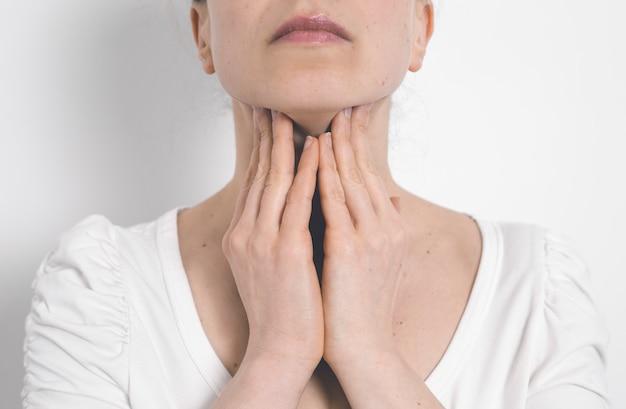 A mulher tem um distúrbio da tiróide. dor de garganta. glândulas inflamadas.
