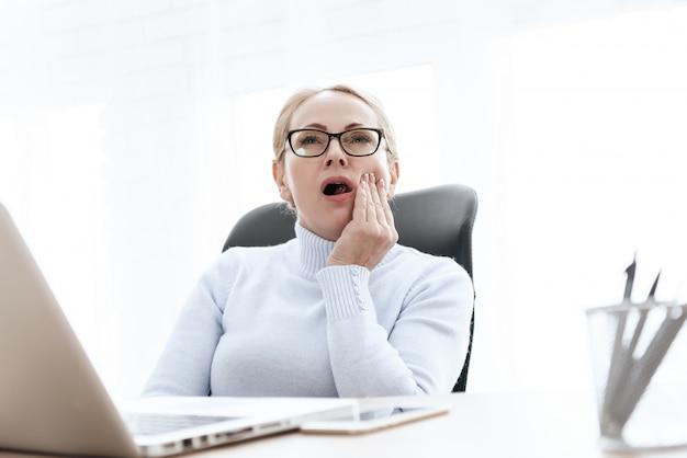 A mulher tem uma dor de dente. ela se sente mal.