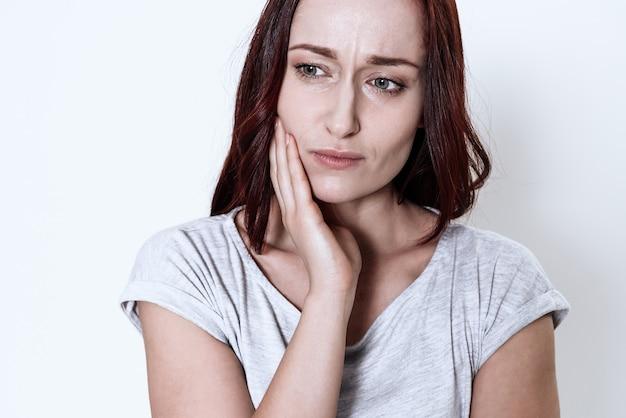 A mulher tem uma dor de dente.
