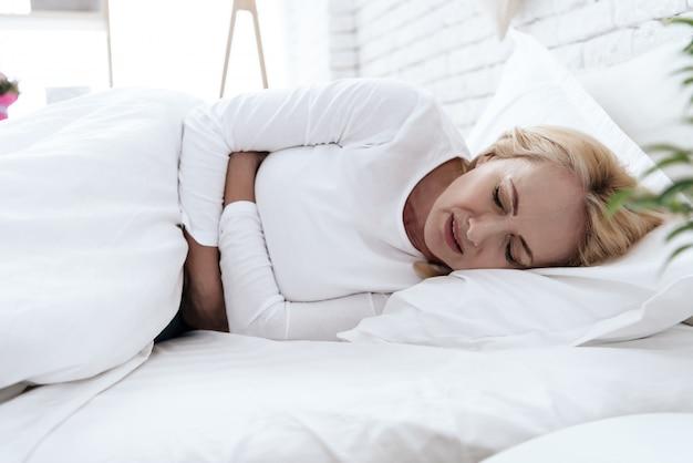 A mulher tem uma dor de estômago deitada na cama.