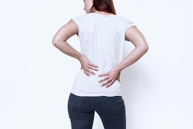 A mulher tem uma dor nas costas. ela se sente mal.