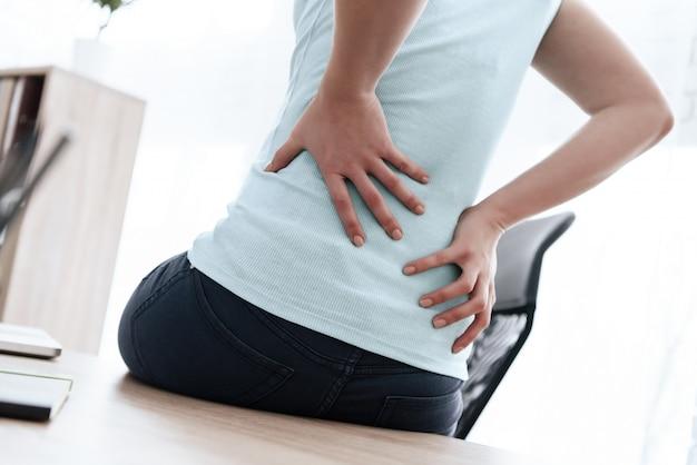 A mulher tem uma dor nas costas no escritório.