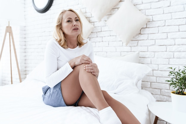A mulher tem uma dor no joelho, ela está fazendo uma massagem