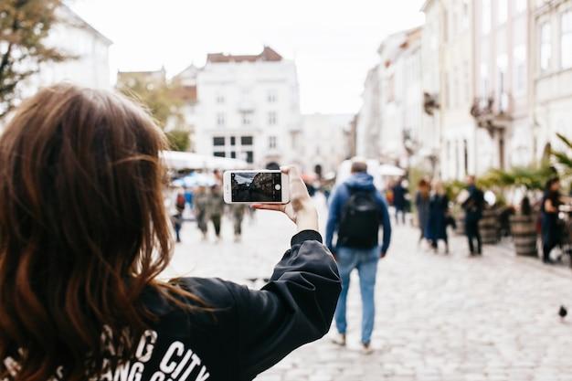 A mulher tira uma foto da praça da cidade em seu smartphone