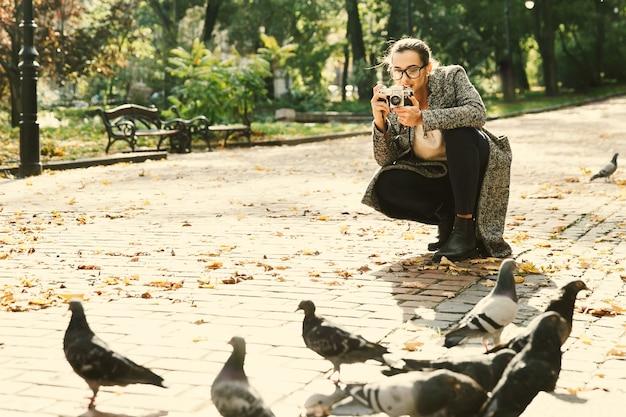 A mulher tira uma foto de pombos em pé no parque