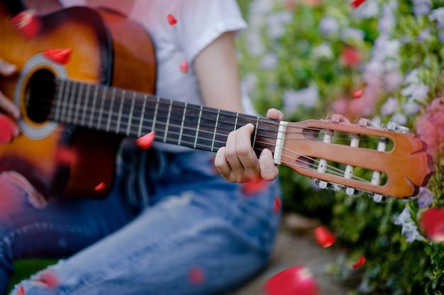 A mulher toca violão alegremente.