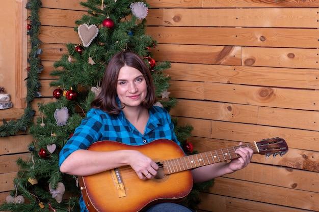 A mulher toca violão no fundo da árvore de natal