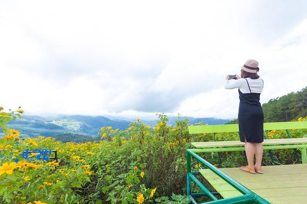 A mulher toma o campo de flor da foto.