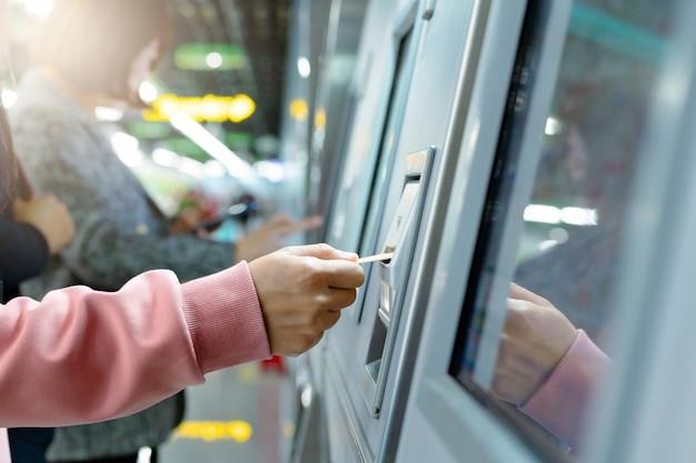 A mulher toma um bilhete de trem após a compra da máquina do bilhete do metro. conceito de transporte