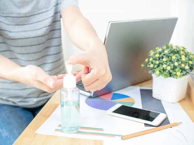 A mulher trabalha em casa usando o notebook, pressionando o gel de álcool da garrafa para limpar as mãos e evitar a propagação do coronavírus durante a crise da covid-19. trabalhar em casa e conceito de saúde