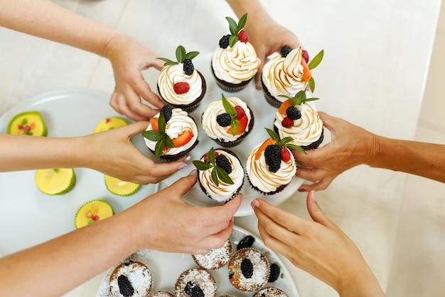 A mulher trata seus amigos com os doces bolos que ela assou.