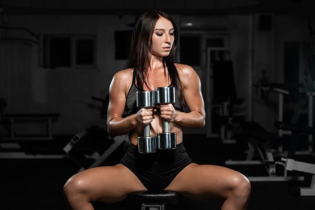 A mulher treina no gym, a mulher atlética treina com dumbbells, bombeando seu bíceps