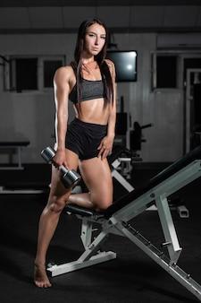 A mulher treina no gym, a mulher atlética treina com dumbbells, bombeando seus bíceps