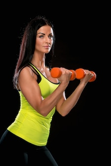 A mulher treinando contra parede preta com halteres vermelhos