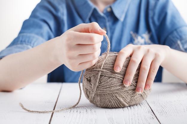 A mulher tricota roupas de lã. agulhas de tricô. fechar-se. lã natural