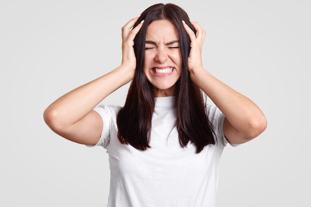 A mulher triste sofre de dor de cabeça, mantém as mãos na cabeça, aperta os dentes, tem expressão estressante, lamenta algo, vai chorar, usa roupa casual, isolada no branco. negatividade