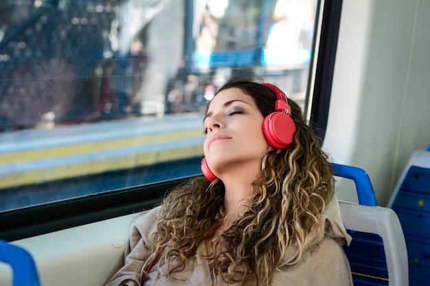 A mulher urbana que dorme em um trem viaja ao lado da janela.