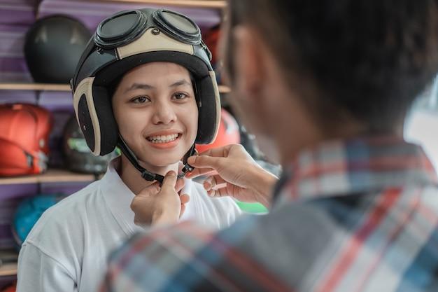 A mulher usa um capacete com a ajuda de um vendedor ao prender a fivela da alça no suporte de exposição do capacete
