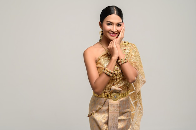 A mulher usa vestido tailandês e as mãos tocam o rosto.