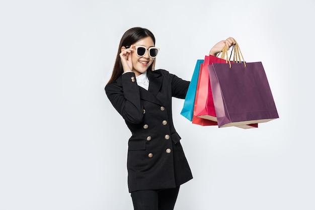 A mulher usando roupas escuras e óculos, junto com muitas bolsas, para ir às compras