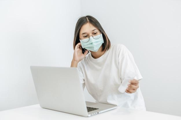 A mulher usando uma máscara de anamai mostra um frasco de gel para lavar as mãos.