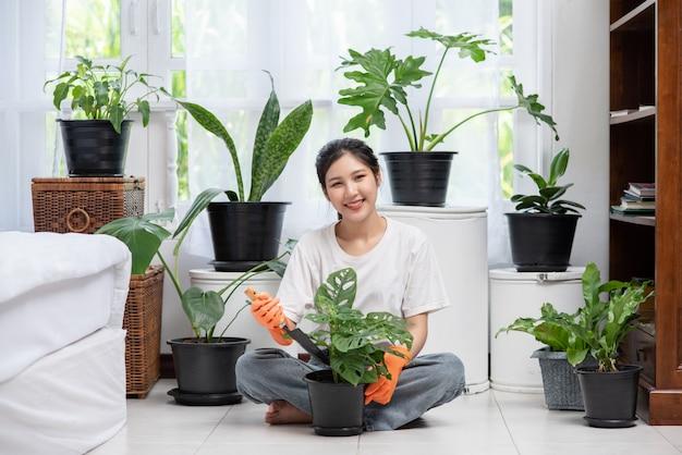 A mulher usava luvas laranja e plantou árvores em casa.
