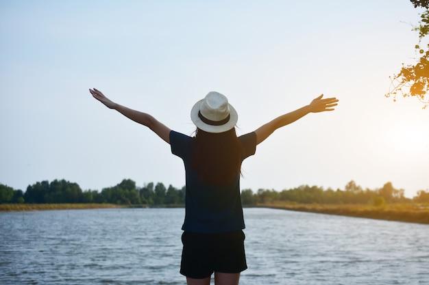 A mulher usava uma camiseta branca e um chapéu, de pé no rio e as duas mãos no céu.