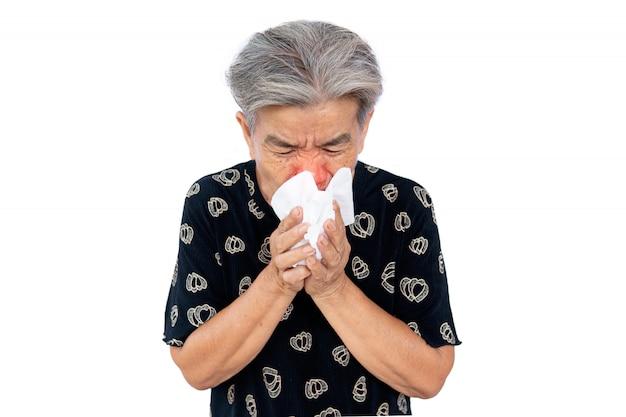 A mulher velha está resfriada, usa um lenço para cobrir a boca quando tosse e espirra,