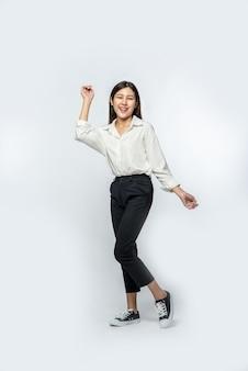 A mulher vestia uma camisa branca e calça escura e fez uma pose divertida