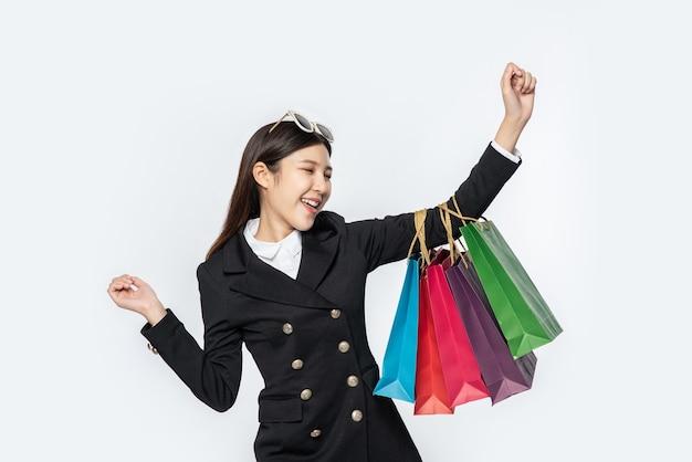A mulher vestindo roupas escuras, junto com muitas bolsas, para ir às compras