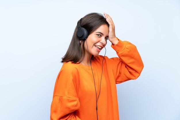 A música de escuta da mulher nova com um móvel sobre a parede azul isolada realizou algo e pretendendo a solução
